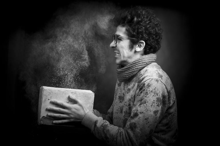 Man holding a dusty book
