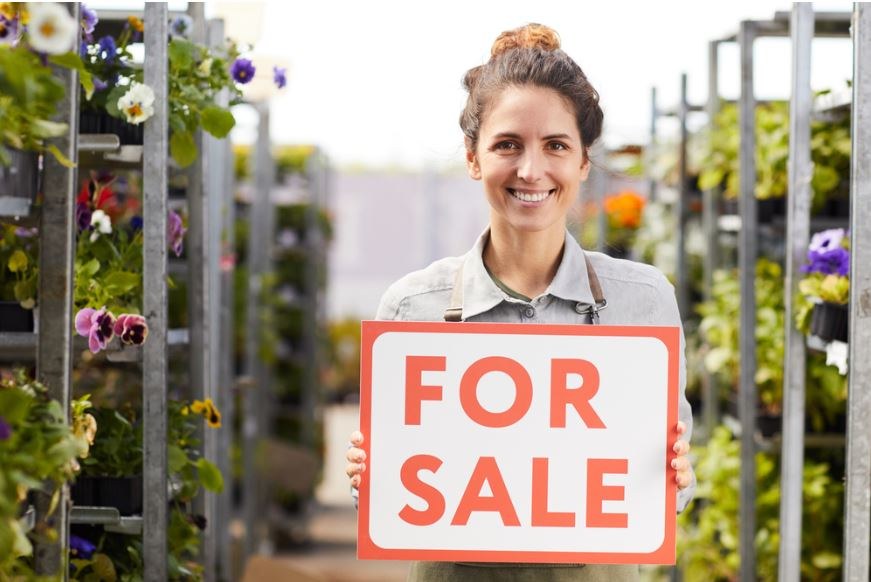 Woman holding business for sale sign