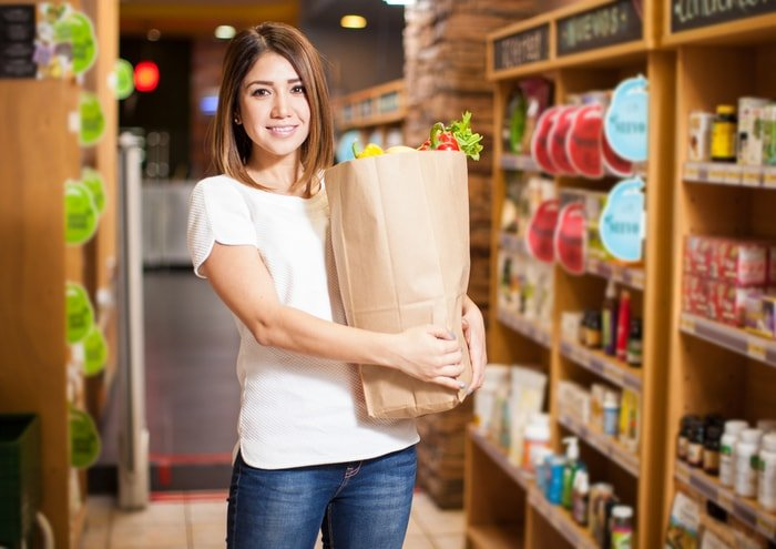Woman holding a grocery bag in a convenience store