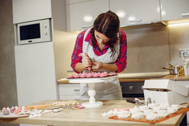Woman putting icing on pastry