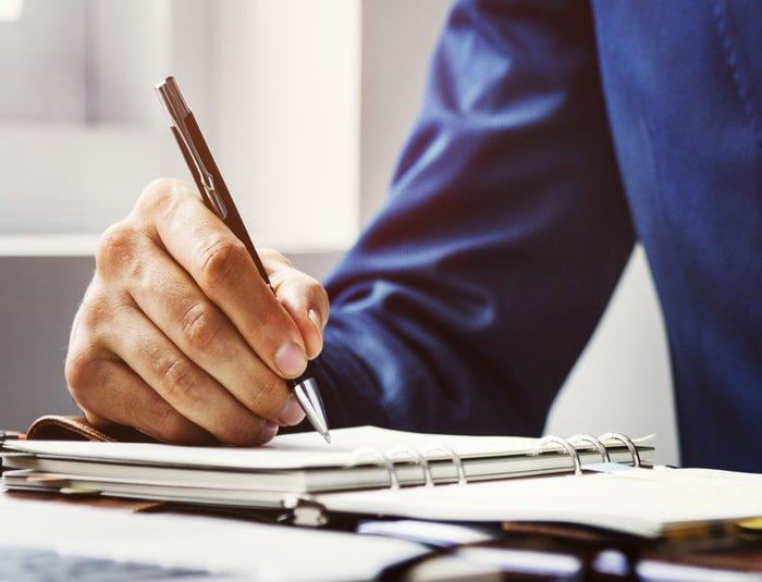 Man writing a business plan for massage business