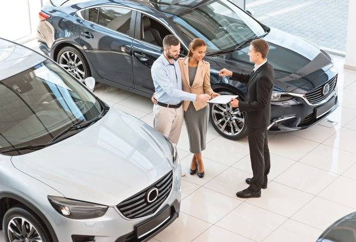 A car dealer talking to interested customers