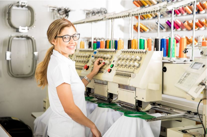 Woman standing behind embroidery machine
