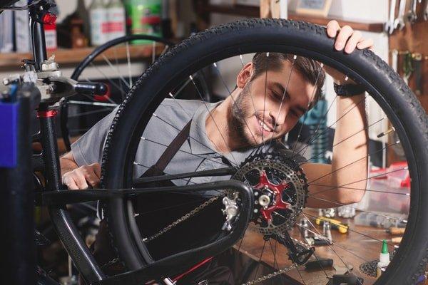 Bike shop mployee holding a bike wheel