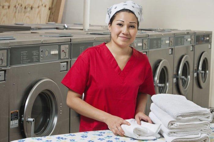 A friendly laundromat employee folding towels in a laundromat shop
