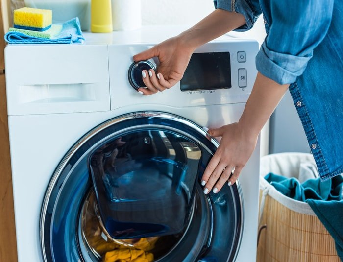 Woman washing clothes using washer with dryer
