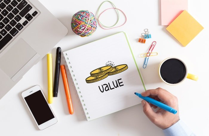 Pens and a notebook on a desk with the word value