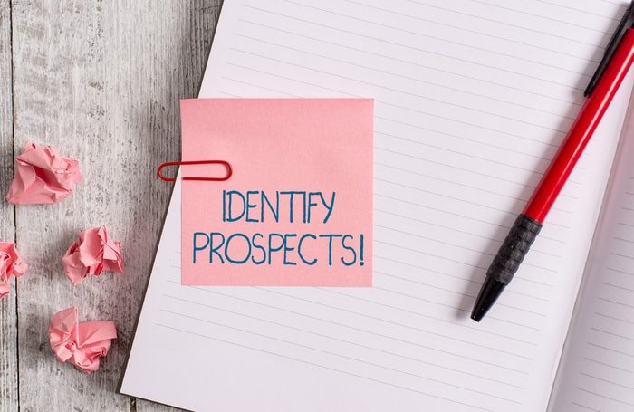 A note and pad on a desk with the word identity prospects