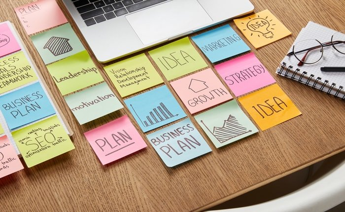 Several sticky notes and a laptop on a desk