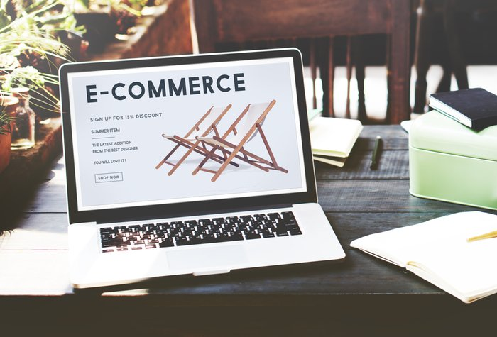 """A laptop showing the word """"e-commerce"""" on a desk"""
