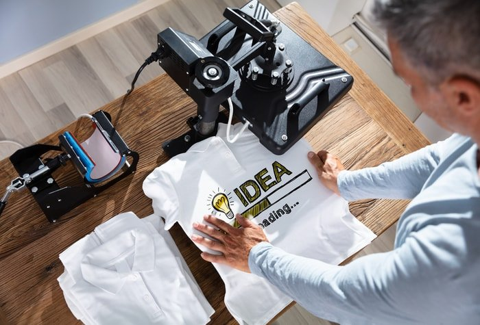 Man printing image on t-shirt in workshop