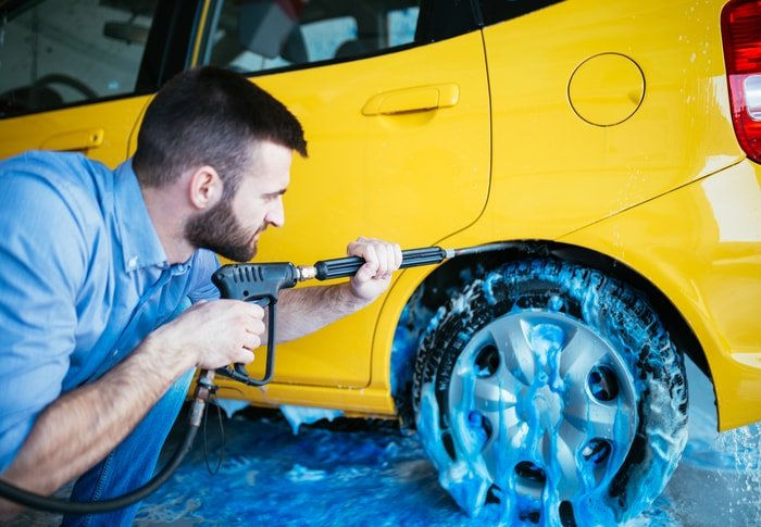 Man cleaning a yellow car using a power spray