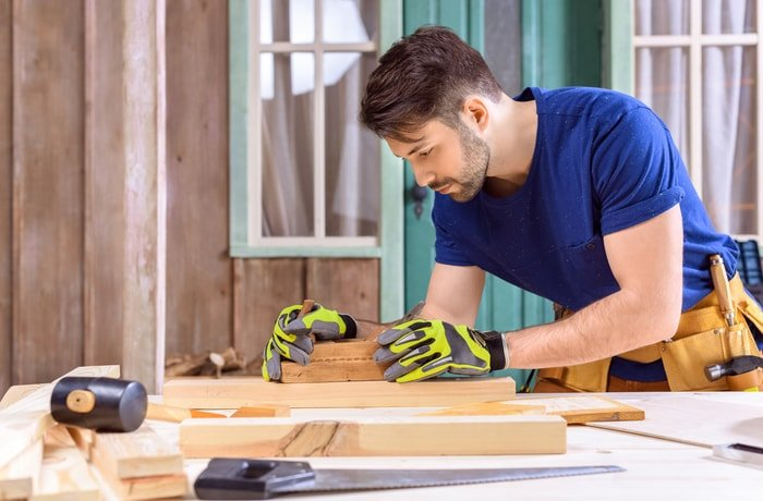 A carpenter wearing a blue shirt and working with wooden plank