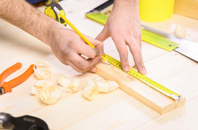 A carpenter taking measurements using a meter on a table.