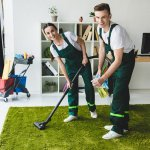 Happy cleaners cleaning a green carpet