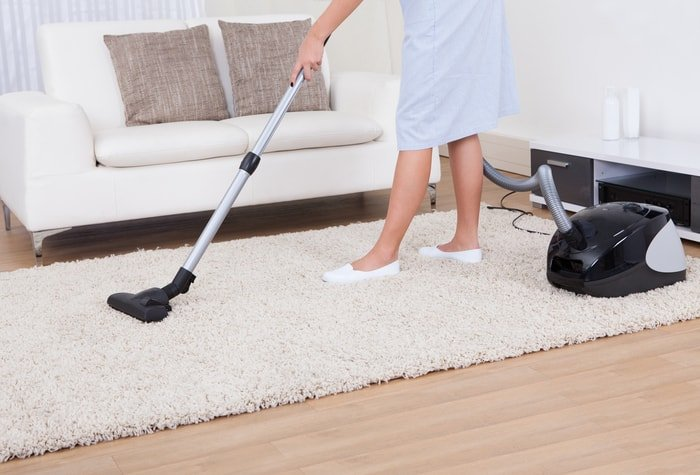 A lady cleaning a carpet using a vacuum cleaner