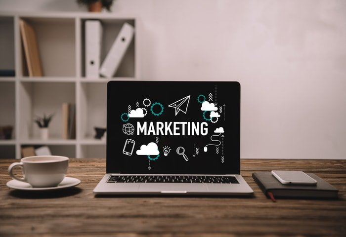 """A laptop on a desk with the word """"marketing' on the screen"""