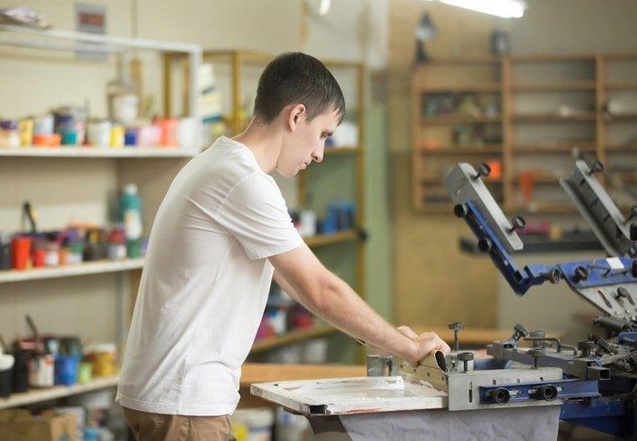 A man screen-printing a t-shirt using a white textile paint