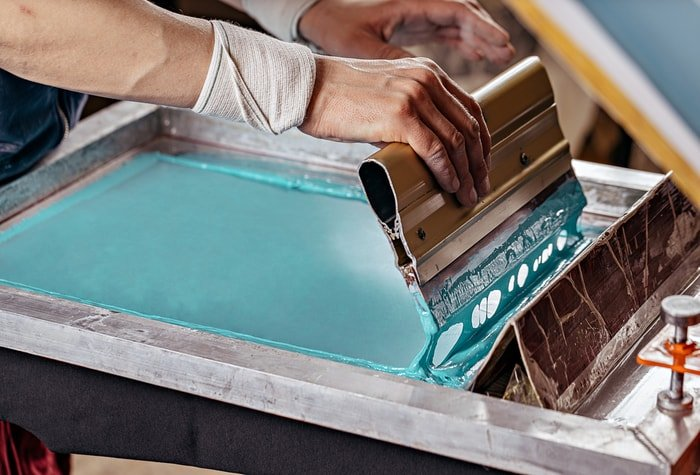 Man screen printing using a blue-green textile paint